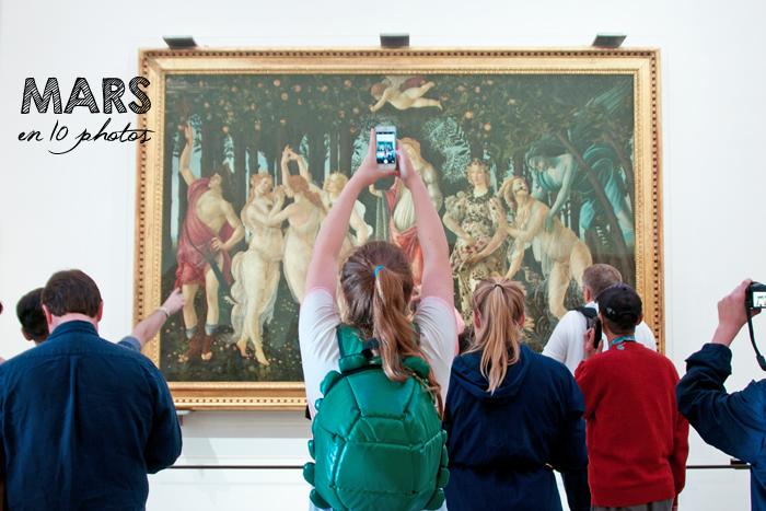 Le printemps de Botticelli dans la galerie des offices à Florence. Au premier plan, des personnes photographient le tableau dont une femme avec un sac à dos en forme de tortue