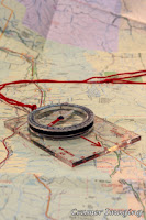 Cramer Imaging's professional quality stock photograph of a map and direction-finding compass laid out on top Like