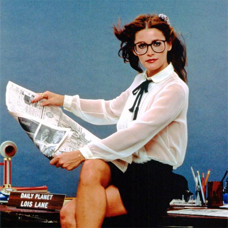 image of Margot Kidder as Lois Lane, sitting on a desk next to her character's nameplate, reading a newspaper
