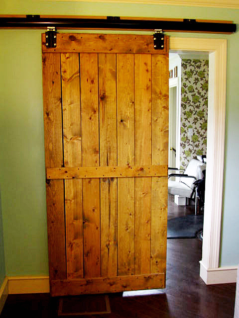 We attached the wood and track to the wall using heavy duty anchors. The door slid right on the end cap was attached and then we were in business!! & tales from a cottage: Our DIY House: Interior Barn Door