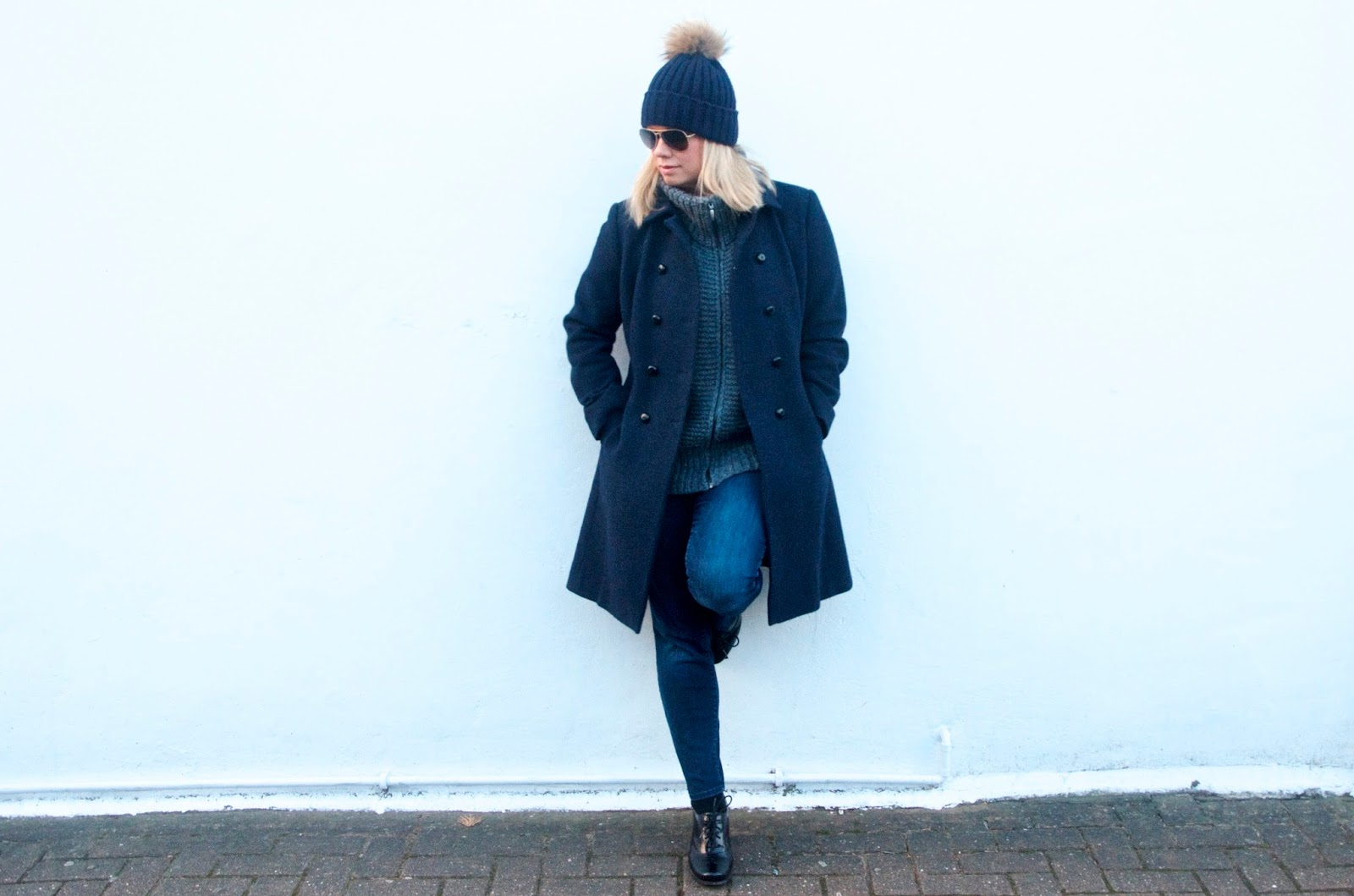 navy coat, grey sweater, skinny jeans and bauble hat with white wall