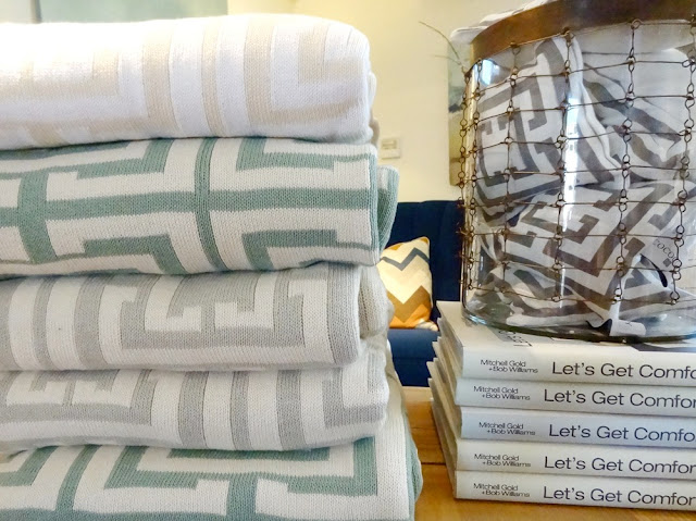 Five COCOCOZY throws are stacked on top of each other, to their right is a stack of books on top of which is a container holding COCOCOZY Lavender Sachets