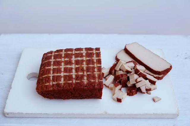 Geräucherter Tofu auf einem Steingut-Schneidebrett in kleine Würfel geschnitten