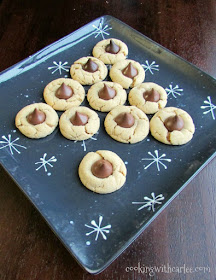 chew peanut butter blossom cookies topped with chocolate kisses arranged to look like Christmas tree
