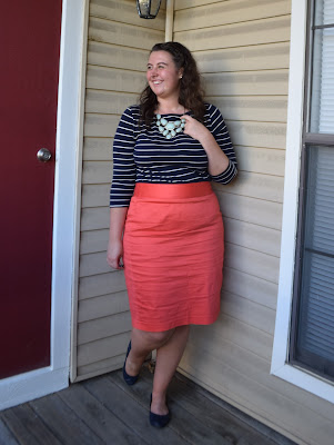 a woman wearing a navy stripe tee, a mint necklace, a coral pencil skirt, and navy flats