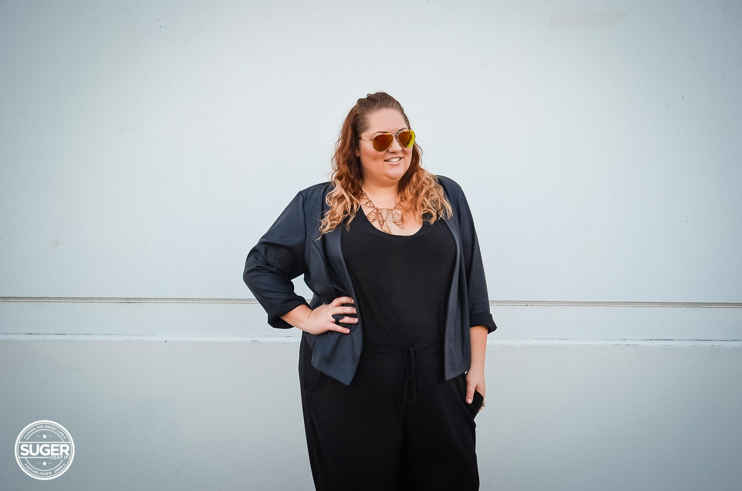 Melissa from Suger Coat It blog wearing sunglasses, black jacket over black dress