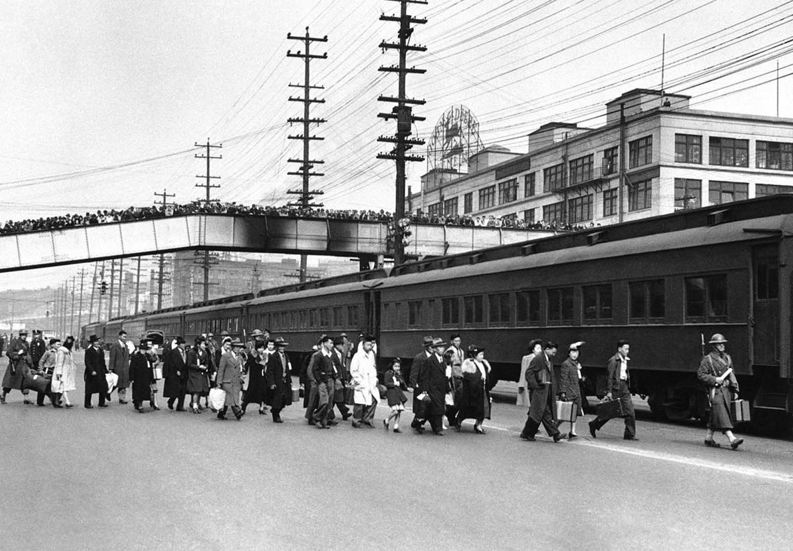 A crowd of onlookers in Seattle jam an overhead walk to witness the mass evacuation of Japanese from Bainbridge Island, Washington, on March 30, 1942. Somewhat bewildered, but not protesting, some 225 Japanese men, women and children were taken by ferry, bus and train to California internment camps. The evacuation was carried out by the U.S. Army.
