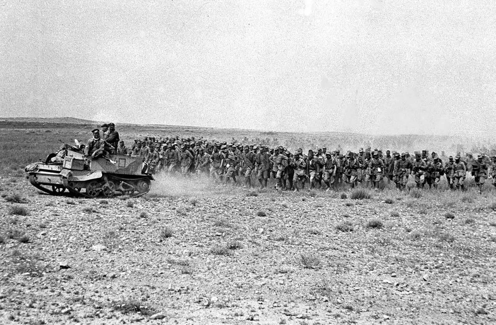 Two thousand Italian prisoners march back through Eighth Army lines, led by a Bren gun carrier, in the Tunisian desert, in March 1943. The prisoners were taken outside El-Hamma after their German counterparts pulled out of the town.