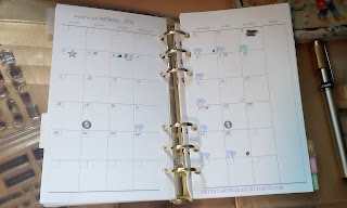The image of a two page spreed month calendar with several letters and symbols stamped onto it.