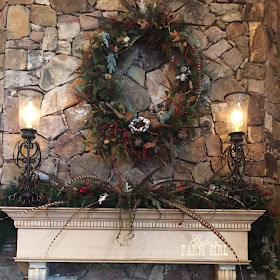Rustic lodge mantle piece and wreath with greenery and feathers