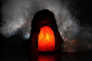 Un enfant regarde une lampe de sel de l'Himalaya.