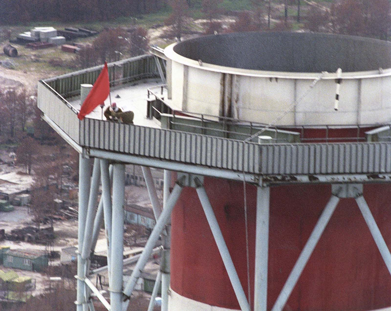 Following orders issued by Soviet authorities to mark the end of cleanup operations on the roof of the No. 3 reactor, three men were requested to post a red flag atop the chimney overlooking the destroyed reactor, reached by climbing 78 meters up a spiral staircase. The flag bearers were sent despite the dangers posed by heavy radiation, and after a group of liquidators had already made two failed attempts by helicopter. The radiation expert Alexander Yourtchenko carried the pole, followed by Valéri Starodoumov with the flag, and Lieutenant Colonel Alexander Sotnikov with the radio. The whole operation was timed to last only 9 minutes, given the high radiation levels. At the end, the trio were rewarded with a bottle of Pepsi (a luxury in 1986) and a day off.