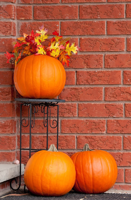 Pumpkins with fall leaves grace the outside entrance of a brick home.
