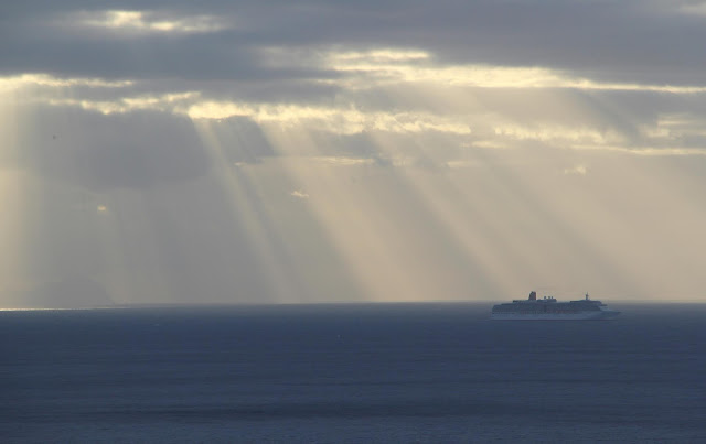 the Aurora cruise ship approaches by sunbeams