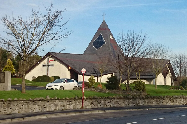 Modern style church building with centre spire and meeting rooms at the sides - with a car parked outside, and a bus-stop.   Also has external Christmas lights above the cross on a gable wall.