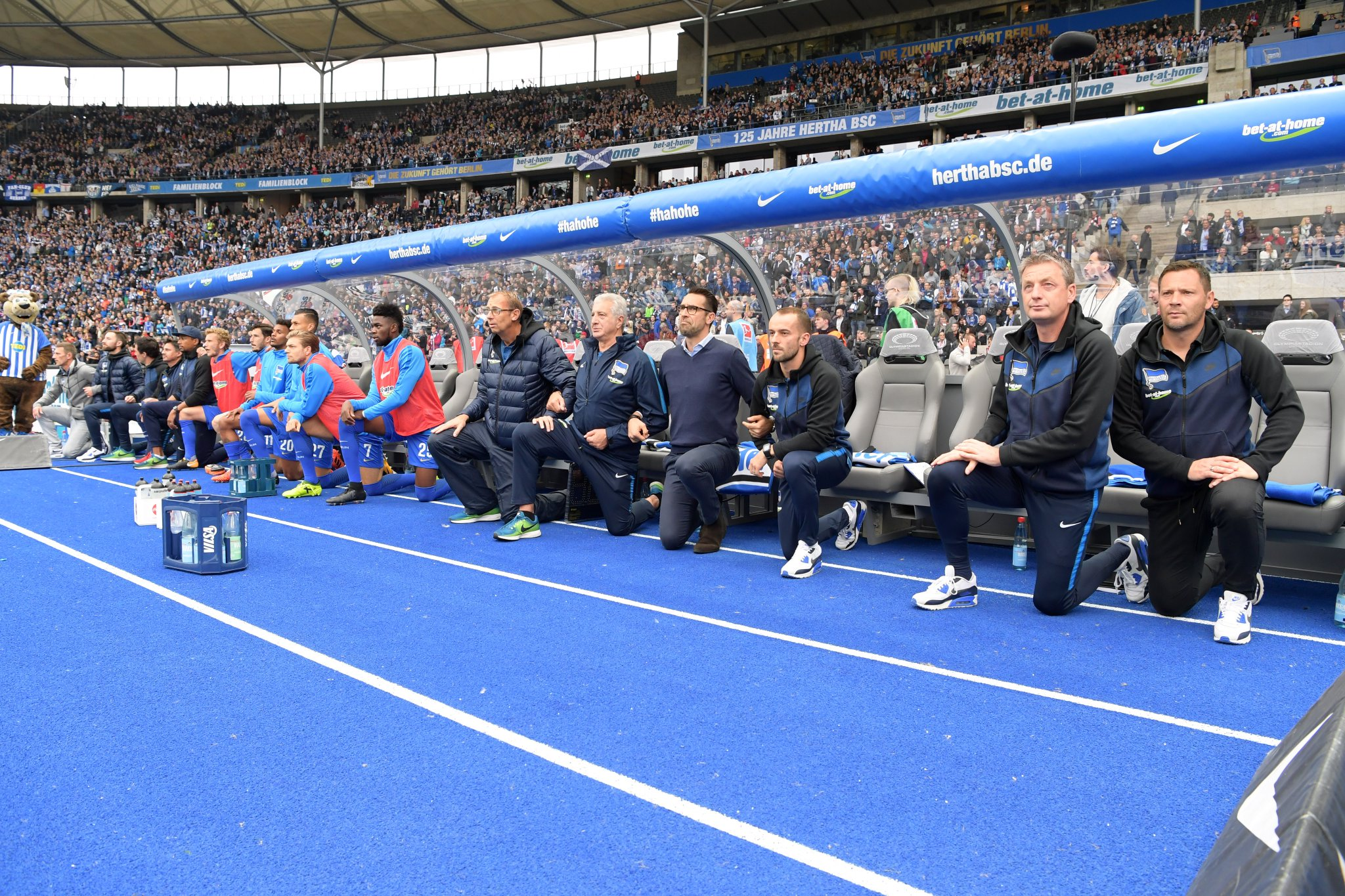 Hertha Berlin coaches, staff and substitutes take a knee before their Bundesliga match against Schalke