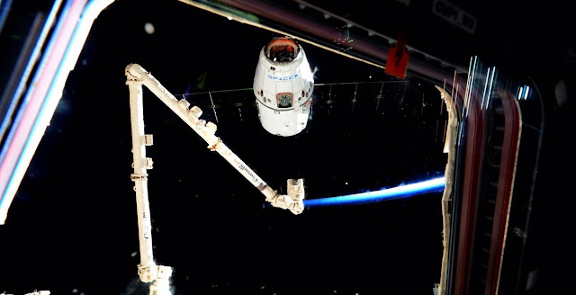 A Dragon out the window: Jeff Williams controls the robotic Canadarm2 to grab Dragon from its free-drift. Photo Credit: NASA