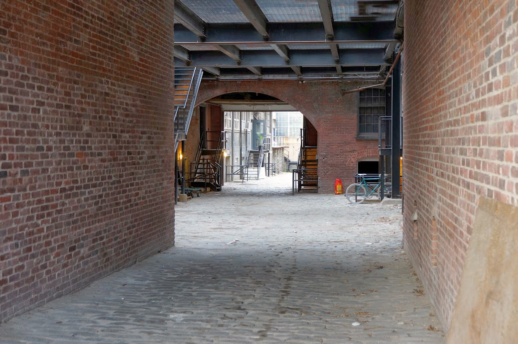 Looking through a corridor from the street to into the courtyard of the Greenpoint Manufacturing and Design Center