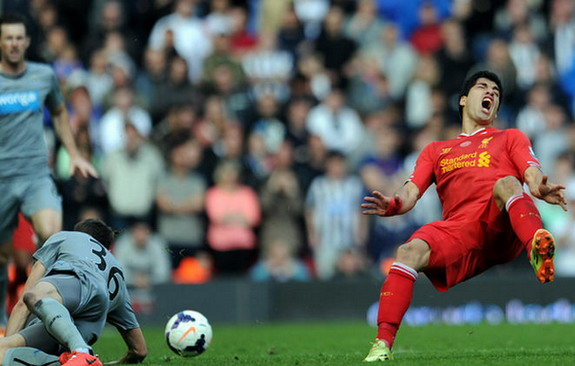 Liverpool forward Luis Suárez is fouled by Newcastle player Paul Dummett