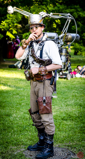Steampunk Man with strange contraption/gadget backpack. Mechanical arm, doll's head, etc.