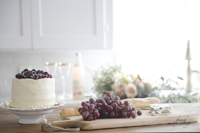 kitchen with berry topped cake and grapes on the island and flowers in the sink