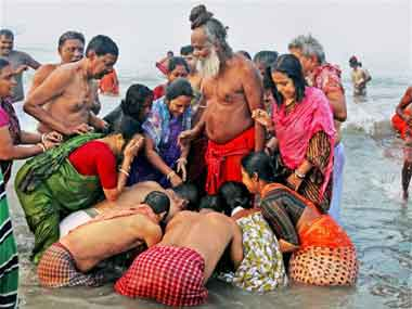 Pilgrims seeks blessings from a Sadhu after a holy dip at Sagar Island on the occasion of Makar Sankranti