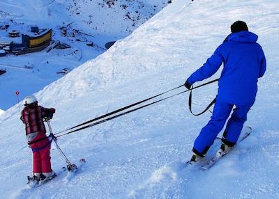 Niña recibe ayuda para esquiar