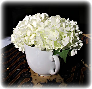 flowers in teacup white pom poms