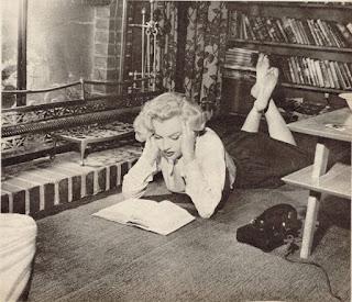 Marilyn Monroe leyendo un libro en su casa