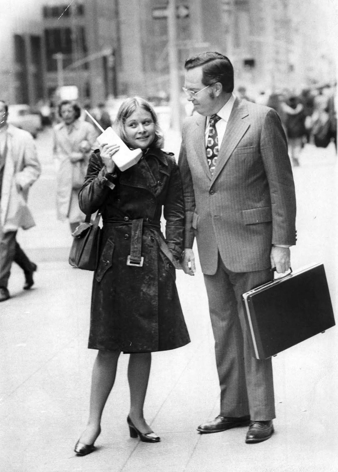 Jeanne Bauer walks with a DynaTAC on 6th Avenue in New York, accompanied by John Mitchell, the Motorola engineer behind the phone. 1973.
