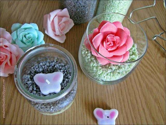 Dwie ozodby z kamyczkami oraz świeczką i kwiatkiem