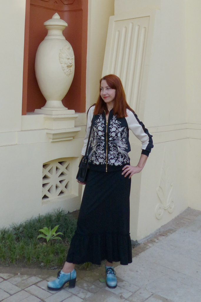 Embroidered bomber worn over black maxi dress