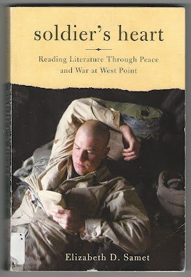 picture shows soldier in combat uniform laying down, relaxing, reading a book