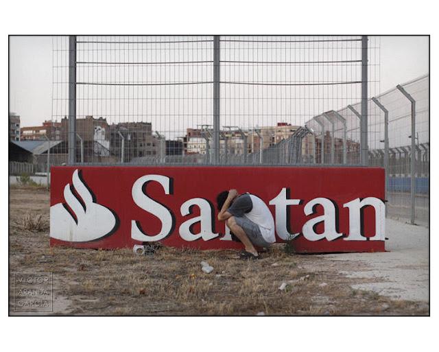 """Fotografía de un cartel de publicidad del Banco de Santander con una persona colocada delante de tal manera que lo que se lee en el cartel es """"satán"""""""