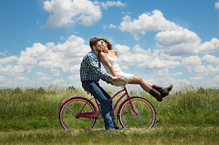 a couple in a relationship on a bike kissing