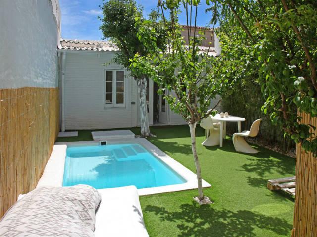 patio con piscina pequeña y césped artificial
