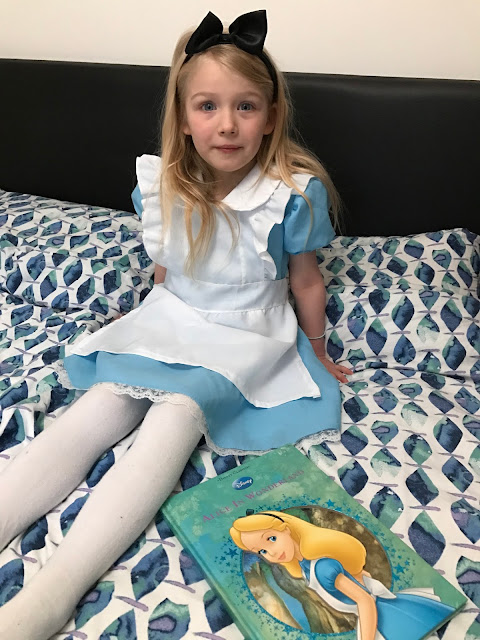 A 5 year old girl in a pale blue dress with white apron and white tights and a black hairband sitting next to a Disney Alice In Wonderland book