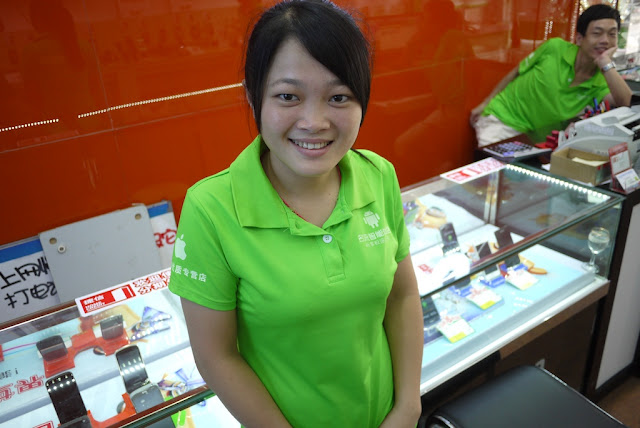 Employee wearing green store shirt with Android and Apple logos.