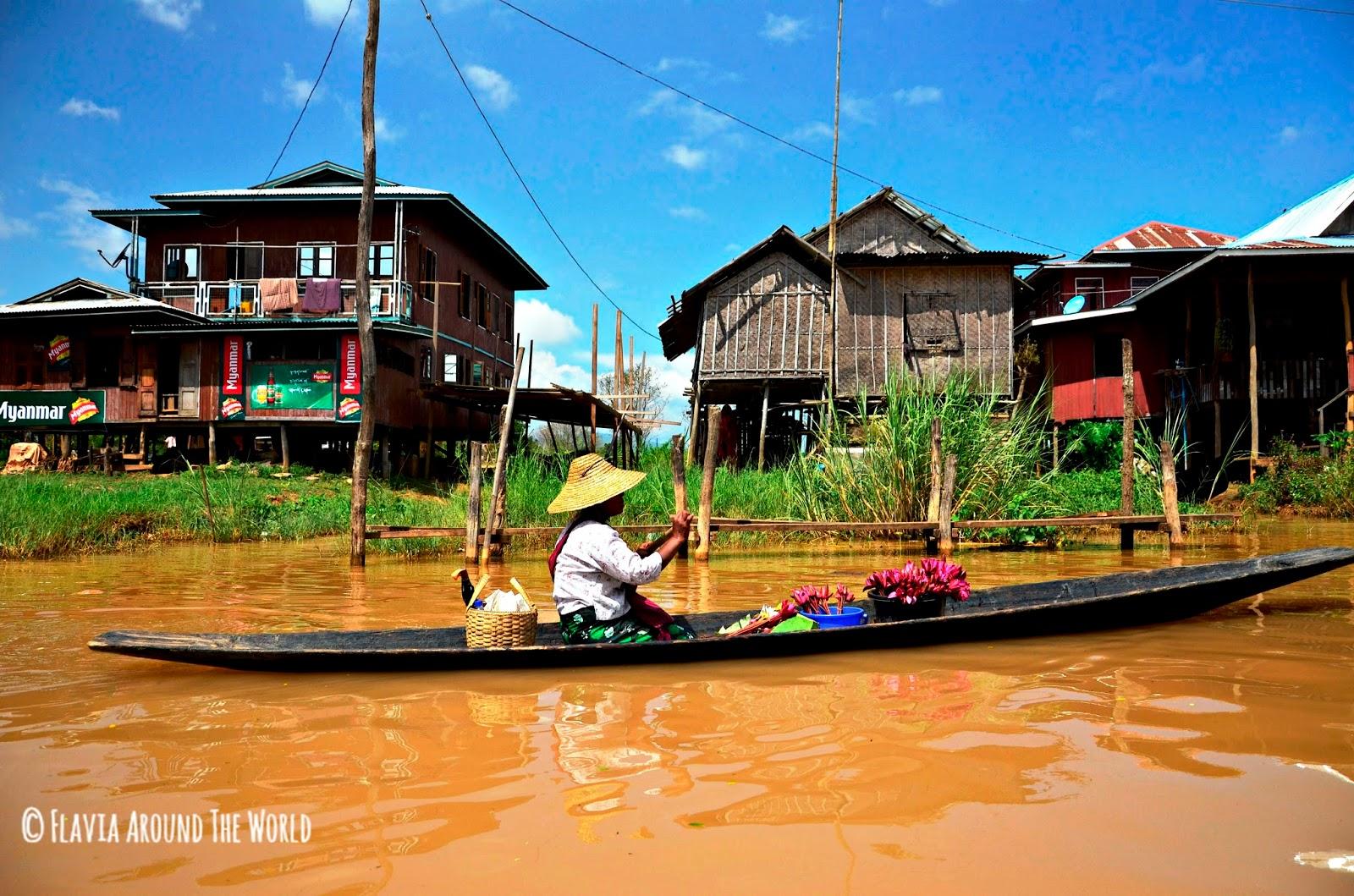 Mujer en barca vendiendo flores por el lago Inle
