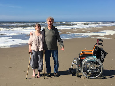 Corina Duyn standing on the beach with her walking sticks beside her brother and her wheelchair