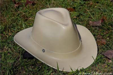 khaki cowboy helmet sitting on grass