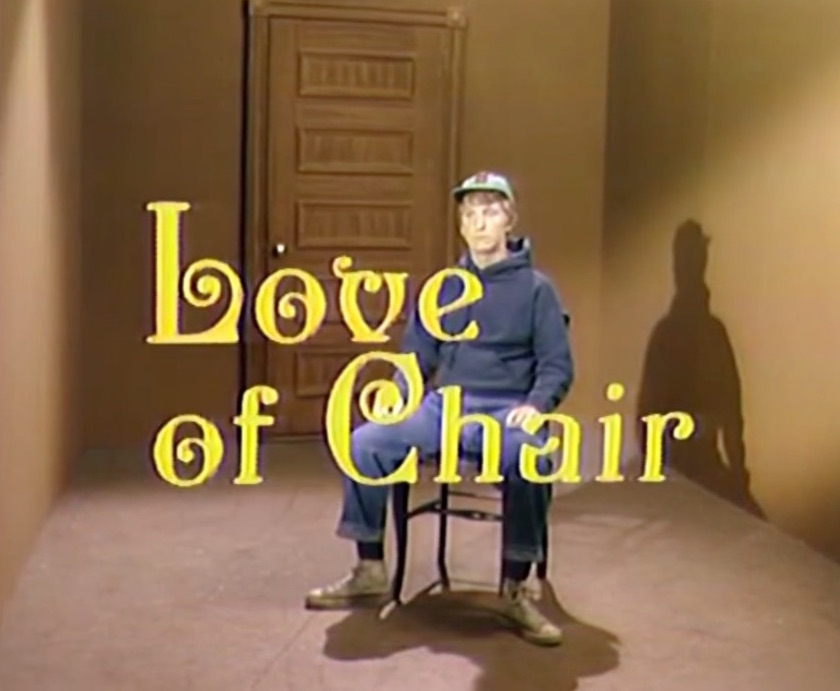 The words 'Love of Chair' in yellow over scene of young man in baseball cap sitting on a chair in a small, empty room