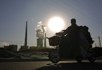 Three-wheeler goes past coal power station (Credit: AP Photo/Andy Wong) Click to Enlarge.