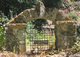 "Stone arch with an iron gate and a wooden sign that says ""Go Away,"" Stevens Canyon Road, Cupertino, California"