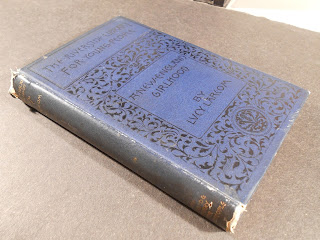 Image of cover and spine of A New England Girlhood as described in the text. The cover is dark blue with black lettering and floral design on front cover. The spine is stamped with gold lettering.