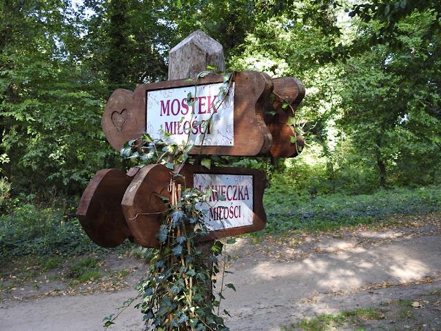 drewniane wskazówki prowadzące do mostka miłości