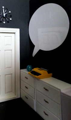 Entrance to a one-twelfth scale modern miniature co-working space, showing a whiteboard on the wall above a row of drawers. Displayed on the drawers is a yellow typewriter.