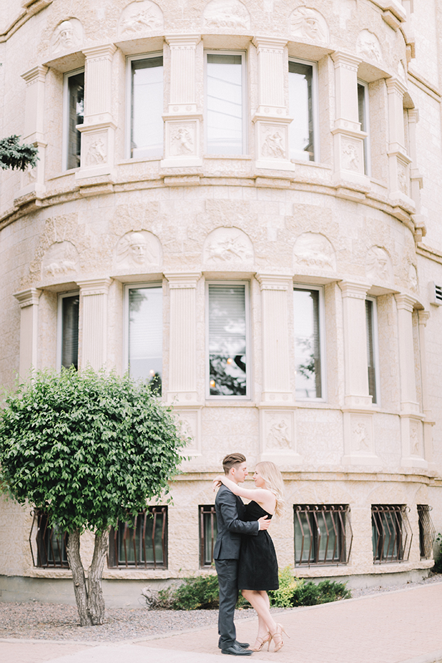 Romantic photoshoot in front of Fort Gary Place, Winnipeg.  Couples outfit idea: classic little black dress and charcoal grey suit.