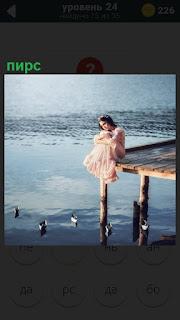 На краю пирса сидит девушка в платье склонив голову, думает о своем