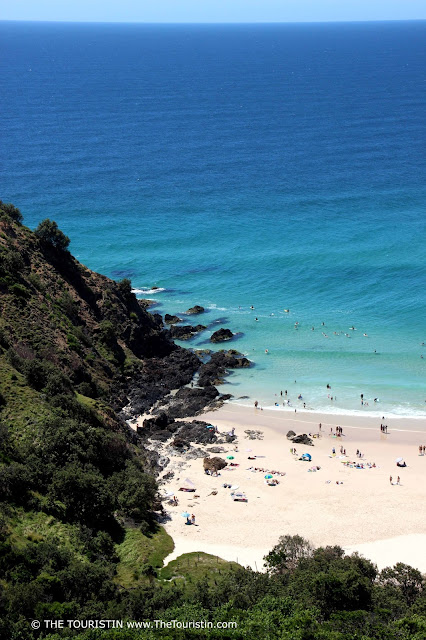 Swimmers and surfers on a white sand beach and in the green-blue coloured ocean next to green vegetation on a hill.